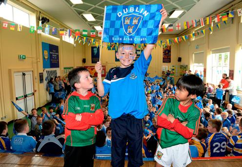 Mayo fans Mickey Collins (on left) and Timothy Brody with Dubs fan Daniel Halpin at Drimnagh Castle Primary School in Dublin. Photo: Caroline Quinn