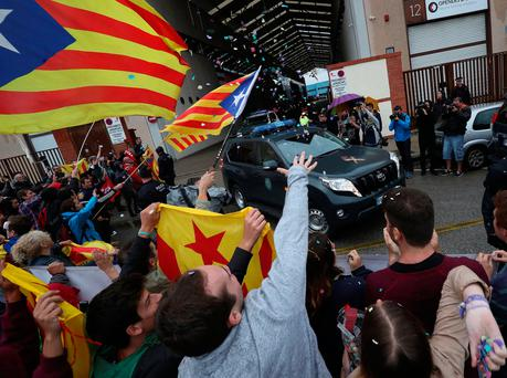 Demonstrators shout and wave Catalan separatist flags as civil guards leave a printing facility after raiding it in search of ballot papers in Sant Feliu de Llobregat, outside Barcelona. Photo: Reuters