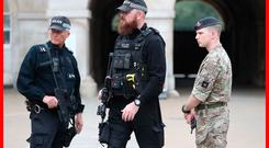 Armed police officers and a soldier on duty at the entrance to Horse Guards in Whitehall, central London, as Operation Temperer is enacted after security experts warned another terrorist attack could be imminent Photo: Jonathan Brady/PA Wire