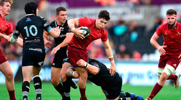 Alex Wootton of Munster is tackled by Paul James of Ospreys