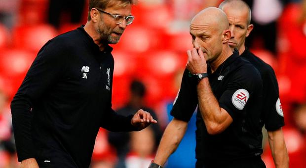 Liverpool manager Jurgen Klopp with referee Roger East after the match