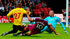 Sergio Aguero squeezes his third goal of the afternoon past Watford goalkeeper Heurelho Gomes at Vicarage Road. Photo: PA Wire