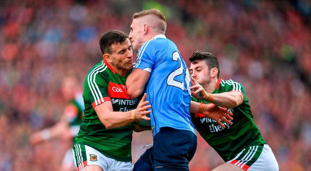 Eoghan O'Gara of Dublin in action against Jason Doherty, left, and Brendan Harrison of Mayo during the GAA Football All-Ireland Senior Championship Final match between Dublin and Mayo at Croke Park in Dublin.