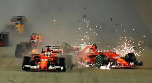 Ferrari's Kimi Raikkonen (right) crashes as Sebastian Vettel leads yesterday's race. Photo: Getty Images