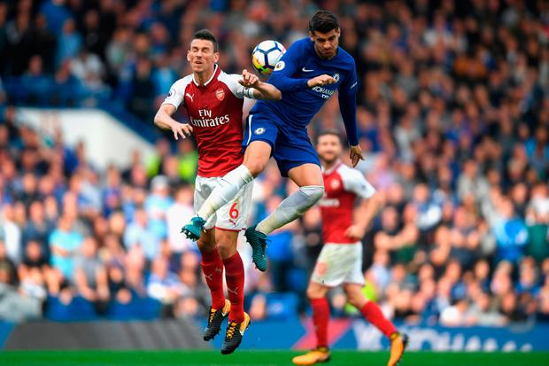 Laurent Koscielny of Arsenal and Alvaro Morata of Chelsea battle for possession in the air. Photo by Mike Hewitt/Getty Images