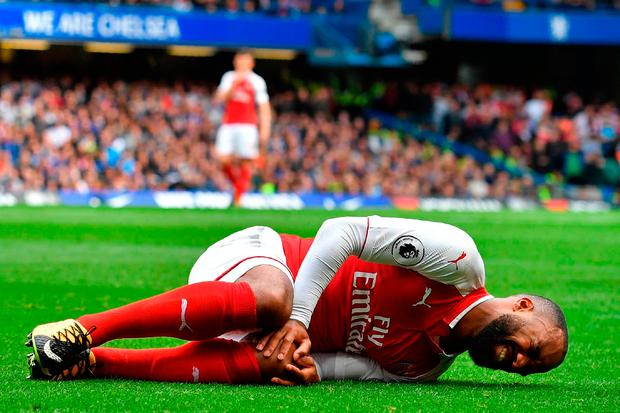 Arsenal's French striker Alexandre Lacazette lies injured after a collision with Chelsea's Nigerian midfielder Victor Moses. Photo: Getty Images