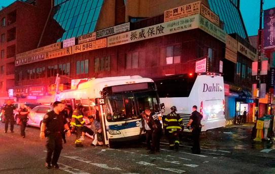 NYPD's 109th Precinct, officers respond to a collision involving two buses on Main Street in the Queens borough of New York, Monday, Sept. 18, 2017. The Fire Department of New York said several been hurt, some of them severely, when a city bus and a tour bus collided in the Flushing neighborhood. (NYPD's 109th Precinct via AP)