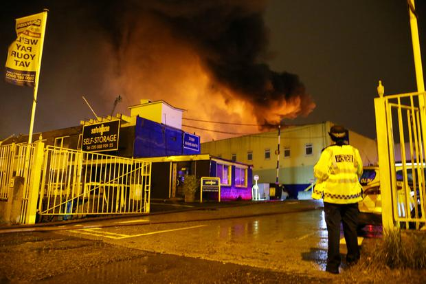 Police stand guard as firefighters (unseen) tackle a fire at a warehouse in Tottenham, north London, Britain, September 18, 2017. REUTERS/Tom Jacobs