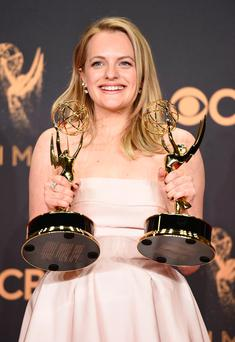 Elisabeth Moss poses in the press room with her awards for outstanding lead actress in a drama series and outstanding drama series for 'The Handmaid's Tale' at the 69th Primetime Emmy Awards. Photo: Jordan Strauss/Invision/AP