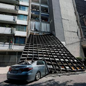 A damaged car is seen outside a building after an earthquake in Mexico City, Mexico September 19, 2017. REUTERS/Claudia Daut