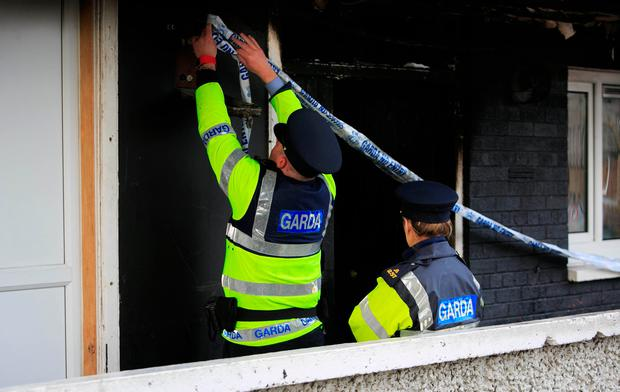 Gardaí at the scene of the fire in the first-floor flat in Inchicore, Dublin, yesterday. Photo: Gareth Chaney