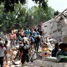 People remove debris of a collapsed building looking for possible victims after the quake. Photo: AFP/Getty Images