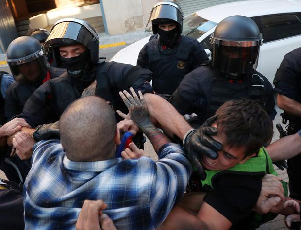 Catalan police officers scuffle with protestors outside a Unipost office which was raided in search of material for the proposed October 1 referendum, in Terrassa, Spain, September 19, 2017. REUTERS/Albert Gea