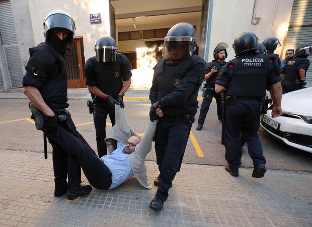 Catalan police officers remove a protestor from the street outside a Unipost office which was raided in search of material for the proposed October 1 referendum, in Terrassa, Spain, September 19, 2017. REUTERS/Albert Gea