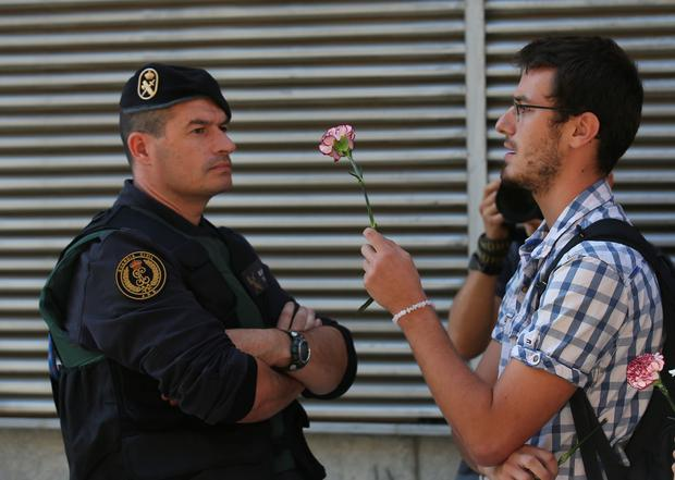 A man holds up a carnation next to a Spanish civil guard during a raid on a Unipost office in search of material for the proposed October 1 referendum, in Terrassa, Spain, September 19, 2017. REUTERS/Albert Gea
