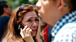 A woman tries to reach people on her cellphone after she evacuated with others to Paseo de la Reforma Avenue after an earthquake in Mexico City, Tuesday, Sept. 19, 2017. A powerful earthquake jolted central Mexico on Tuesday, causing buildings to sway sickeningly in the capital on the anniversary of a 1985 quake that did major damage. (AP Photo/Marco Ugarte)