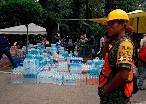A soldier stands guard next to donations of bottled water for rescue workers and victims next to a collapsed building after earthquake in Mexico City, Mexico September 20, 2017. REUTERS/Henry Romero