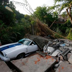 A car sits partially buried by debris from a 7.1 earthquake, in Jojutla, Morelos state, Mexico, Wednesday, Sept. 20, 2017. (AP Photo/Eduardo Verdugo)