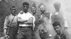 Jerry Corbett crouching with fellow workers in the early days of the Rural Electrification Scheme. Photo: ESB Archive
