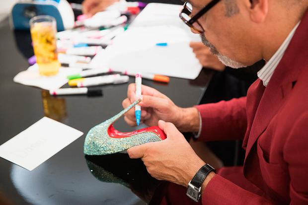 Fashion designer Christian Louboutin paints an autograph during a personal appearance at Nordstrom Downton Seattle on October 17, 2016 in Seattle, Washington. (Photo by Mat Hayward/Getty Images for Nordstrom)