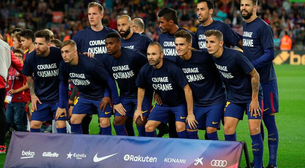 Barcelona players pose for a team group photo wearing shirts in reference to Ousmane Dembele before the match