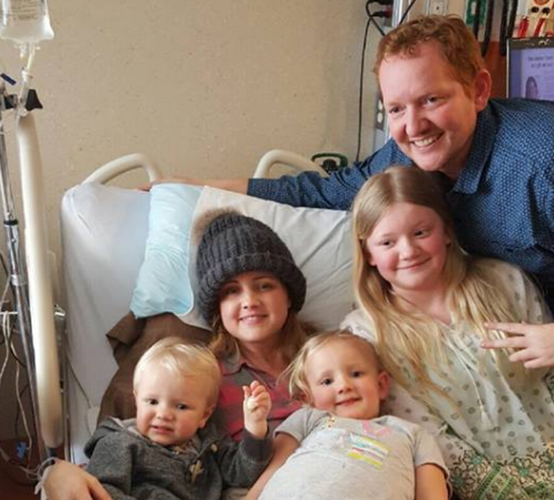 Carrie in the hospital with three of her children and her husband Nick. (Cure 4 Carrie)