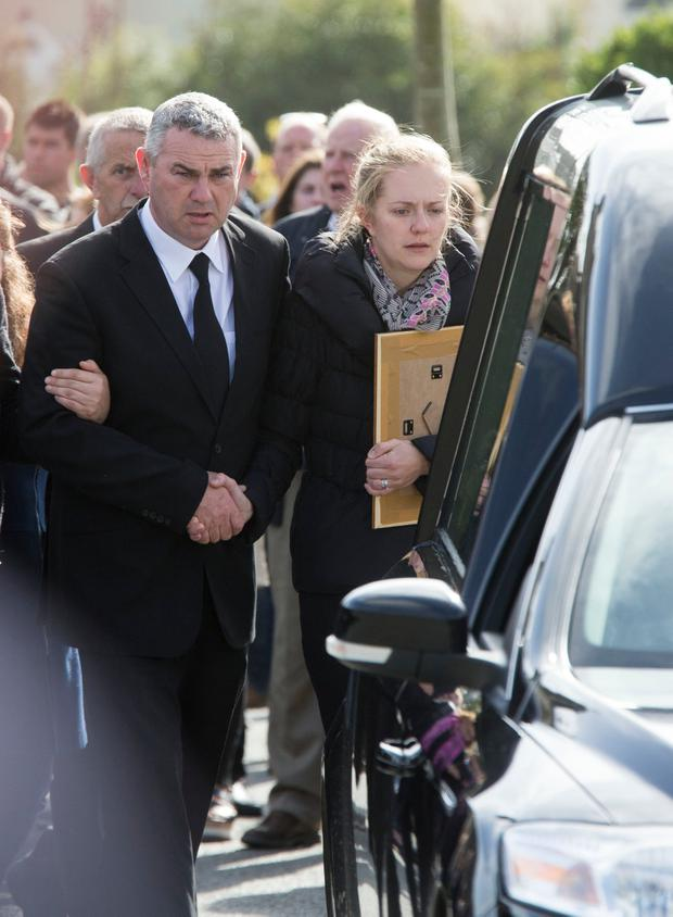 Martin's wife Kerrie Kehoe and his brother Willie John Kehoe walk behind the hearse at St Aidan's Church, Clongeen, Co Wexford, yesterday. Photo: Colin O'Riordan