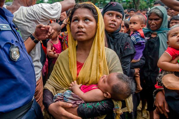 A Rohingya Muslim woman holds her child as she waits to receive aid near Balukhali refugee camp, Bangladesh. Photo: AP Photo/Dar Yasin