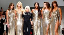 Italian designer Donatella Versace (3L) acknowledges the applause with former top models Carla Bruni (L), Claudia Schiffer, Naomi Campbell, Cindy Crawford and Helena Christensen (R) at the end of Versace Spring/Summer 2018 show at the Milan Fashion Week in Milan, Italy, September 22, 2017. REUTERS/Alessandro Garofalo