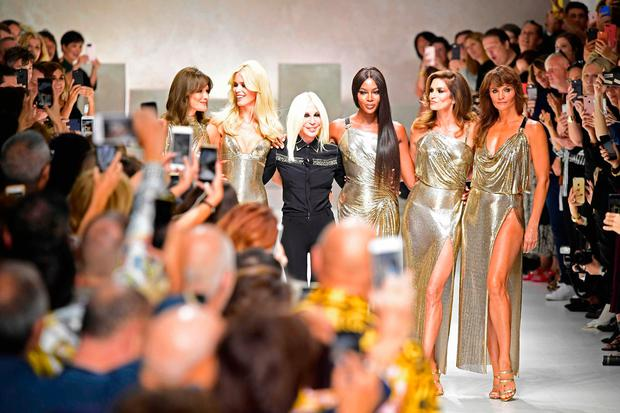 Top models (from left) Carla Bruni, Claudia Schiffer, Italian designer Donatella Versace (C), Naomi Campbell, Cindy Crawford and Helena Christensen walk the runway with at the end of the show for fashion house Versace during the Women's Spring/Summer 2018 fashion shows in Milan, on September 22, 2017. / AFP PHOTO / Miguel MEDINAMIGUEL MEDINA/AFP/Getty Images