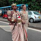 Sri Lankan wedding couple walk along a road as as a bride attempts to set a record for the longest wedding saree, with a length of 3.2 kms (two-miles), in the central district of Kandy on September 22, 2017