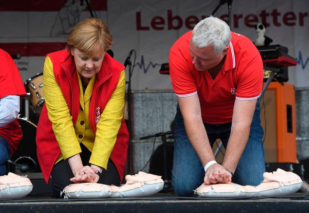 German chancellor Angela Merkel, left, sits atop a resuscitation doll next to Prof. Dr. med. Klaus Hahnenkamp on stage in Greifswald, Germany, Saturday, Sept. 23, 2017. . (Stefan Sauer/dpa via AP)