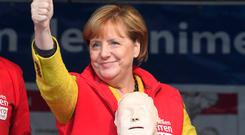 German chancellor Angela Merkel stands on stage in Greifswald, Germany, Saturday, Sept. 23, 2017. During the project week