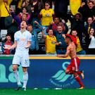 Watford player Richarlison celebrates the winning goal as Federico Fernandez of Swansea screams in frustration. Photo: Getty