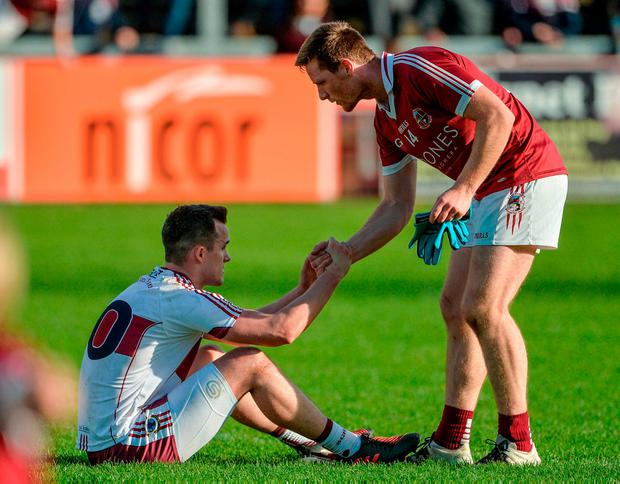 Se McGuigan commiserates with Ballinascreen's Carlus McWilliams after the game. Photo: Oliver McVeigh/Sportsfile