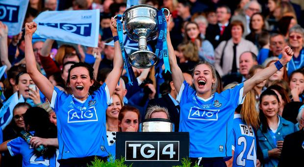 Dublin players Niamh McEvoy, left, and Nicole Owens celebrate with the Brendan Martin Cup after their victory over Mayo. Photo: Brendan Moran/Sportsfile