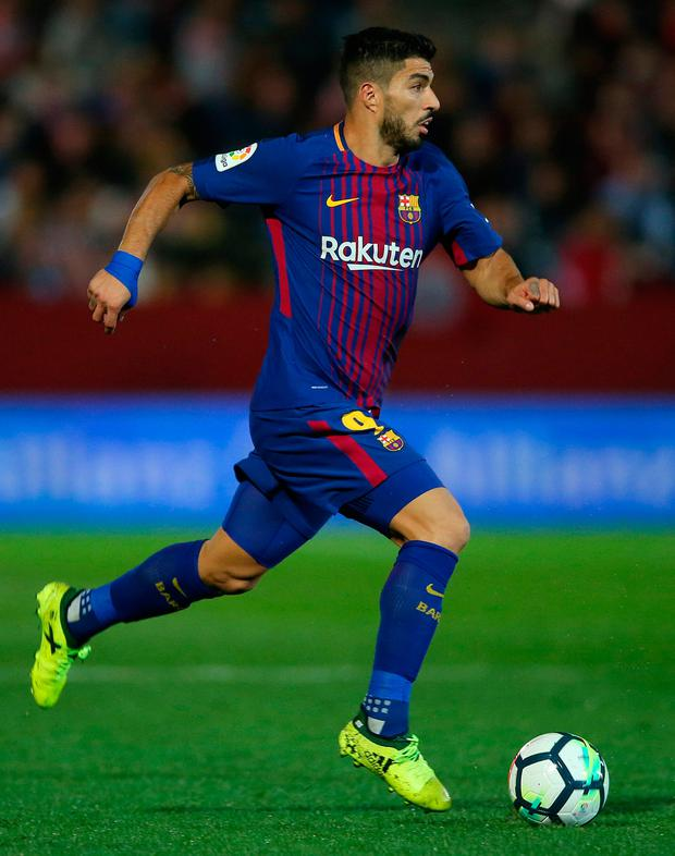 Luis Suarez smashed home a third goal with 20 minutes remaining to maintain their four-point lead at the top of the table. Photo: Reuters/Albert Gea