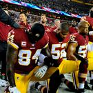 Washington Redskins tight end Niles Paul (84) and linebacker Ryan Anderson (52) and Washington Redskins linebacker Chris Carter (55) kneel with teammates during the playing of the national anthem before the game between the Washington Redskins and the Oakland Raiders