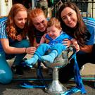 Eoin McNeill (2), from Whitehall in Dublin, sits in the Brendan Martin Cup with Ciara Trant, Lauren Magee and Lyndsey Davey during a visit by the Dublin senior ladies footballers to Temple Street Children's Hospital, in Dublin. Photo: Cody Glenn/Sportsfile
