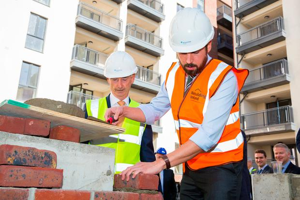 Housing Minister Eoghan Murphy gets his hands dirty as he looks around the Charlemont Street regeneration project with Sean Reilly, of construction company McGarrell Reilly