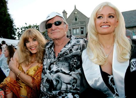 Playboy Magazine founder Hugh Hefner (C) is joined by former girlfriend Barbi Benton (L), and current girlfriend, Holly Madison, during an ESPY Awards pre-party at the Playboy Mansion in Beverly Hills, California in this July 12, 2005 file photo. REUTERS/Robert Galbraith/File Photo
