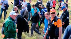 Rory McIlroy retrieves his ball in the rough on the 17th amongst the crowd