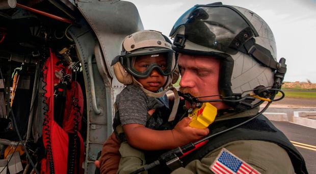 This US Navy handout photo, released September 28, 2017,shows Naval Aircrewman (Helicopter) 2nd Class Brandon Larnard, assigned to Helicopter Sea Combat Squadron (HSC) 22, embarked aboard the amphibious assault ship USS Wasp (LHD 1),as he carries an evacuee off an MH-60S Sea Hawk helicopter following the landfall of Hurricane Maria on the island of Dominica on September 27, 2017. SEAN GALBREATH/AFP/Getty Images