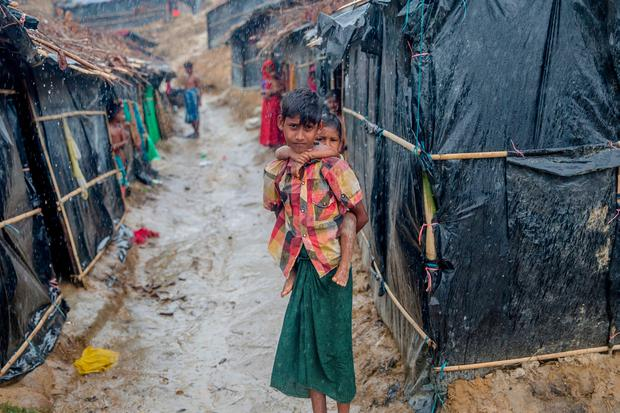 A Rohingya Muslim boy, who crossed over from Myanmar into Bangladesh, holds his brother outside his shelter as it rains in Balukhali refugee camp, Bangladesh, Thursday, Sept. 28, 2017. (AP Photo/Dar Yasin)
