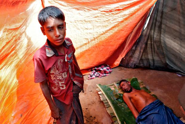 A Rohingya refugee stands beside the remains of his father, whose family says he succumbed to injuries inflicted by the Myanmar Army before their arrival, in Cox's Bazar, Bangladesh, September 29, 2017. REUTERS/Cathal McNaughton