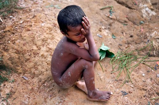 A Rohingya refugee child cries as he sits on the ground in Cox's Bazar, Bangladesh, September 29, 2017. REUTERS/Cathal McNaughton