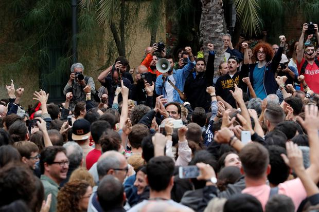 People react as they listen a speech at a courtyard outside a polling station for the banned independence referendum in Barcelona, Spain, October 1, 2017. REUTERS/Yves Herman