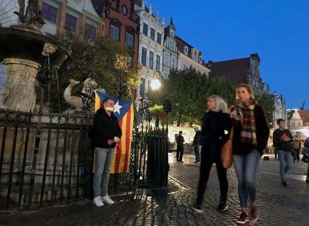 Xavier Canals, a Catalonian living in Poland, protests standing next to a flag in the central square of the old town in Gdansk, Poland, October 1, 2017. REUTERS/Radu Sigheti