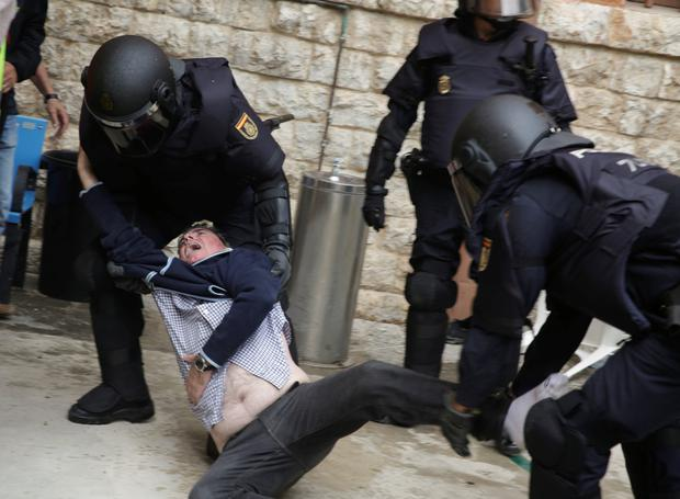 Spanish police scuffle with a man outside a polling station for the banned independence referendum in Tarragona, Spain, October 1, 2017. REUTERS/David Gonzalez NO RESALES. NO ARCHIVES