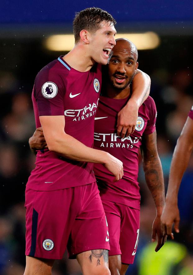 Manchester City centre-half John Stones celebrates at Stamford Bridge with Fabian Delph after the game
